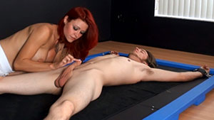 FemDom handjob video performed by busty redhead Catherine Fox on a restrained cum filled cock featured on HandDomination.